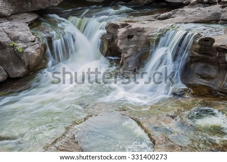 A photography of beautiful waterfall on the rocks - stock photo