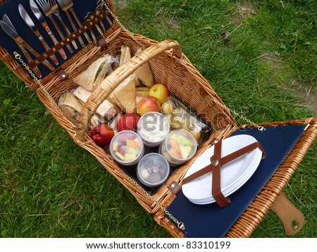 A picnic basket with the ingredients for a lunch in the open air - stock photo