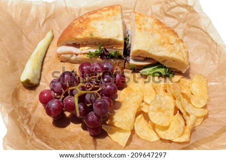 A picnic lunch with a Turkey and Cheese Sandwich on Cheese Bread, Chips, Red Grapes and a Dill Pickle Slice wrapped in deli paper, isolated on white. Deli Sandwiches are a favorite for picnics  - stock photo