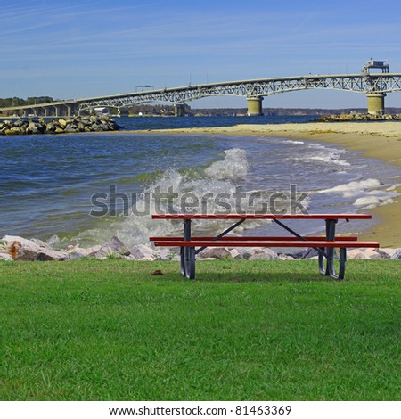 A Picnic table on a summer day along the rock lined shore of Yorktown Beach beach with the George P Coleman Bridge in the background and room for your text. - stock photo
