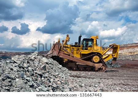 A picture of a big yellow bulldozer at work-site - stock photo