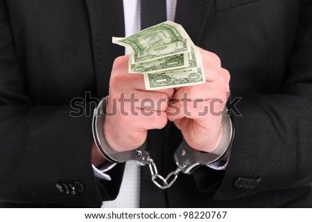 A picture of a businessman in handcuffs holding dollars - stock photo