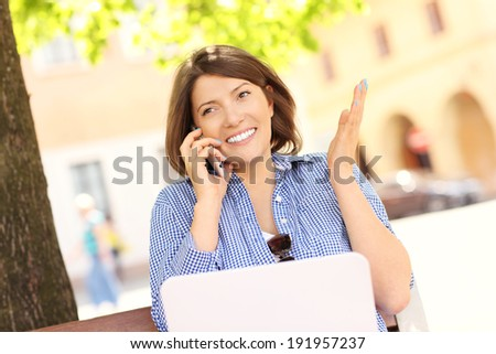 A picture of a businesswoman on the bench with laptop and cellphone - stock photo