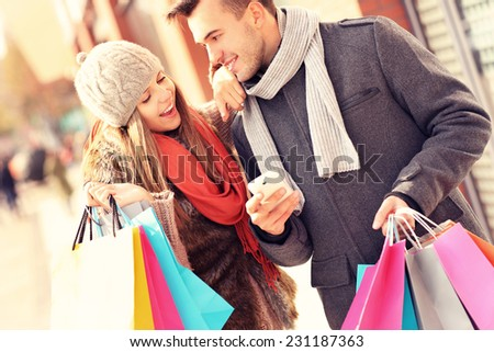 A picture of a couple shopping with smartphone in the city - stock photo