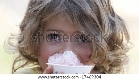 a picture of a cute little girl smiling eating snow cone - stock photo