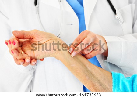 A picture of a doctor checking patient's pulse - stock photo