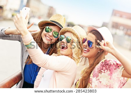 A picture of a group of friends taking selfie and having fun in the city - stock photo