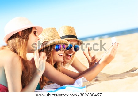 A picture of a group of friends taking selfie on the beach - stock photo