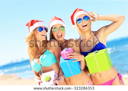 A picture of a group of women in bikini and Santa's hats holding presents on the beach - stock photo