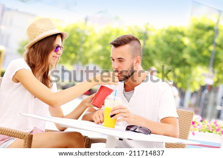 A picture of a happy couple drinking smoothies in an outside cafe - stock photo