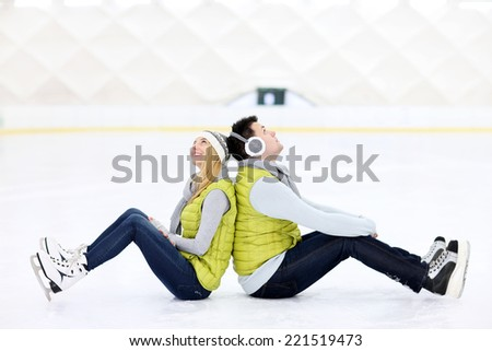 A picture of a happy couple sitting on the skating rink - stock photo