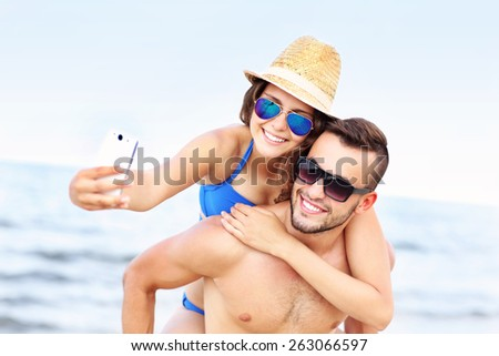 A picture of a happy couple taking selfie at the beach - stock photo