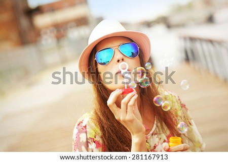A picture of a happy woman blowing soap bubbles in the city - stock photo