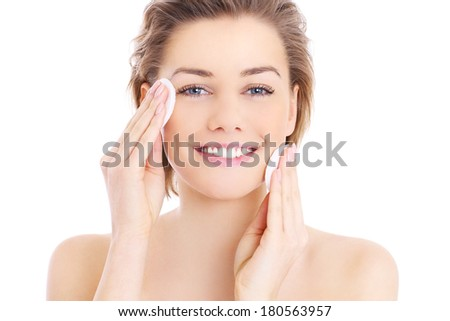 A picture of a happy woman cleaning her face with cotton pads over white background - stock photo