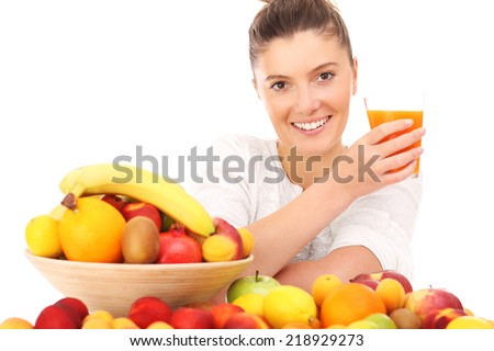 A picture of a happy woman with fruits and a glass of juice over white background - stock photo