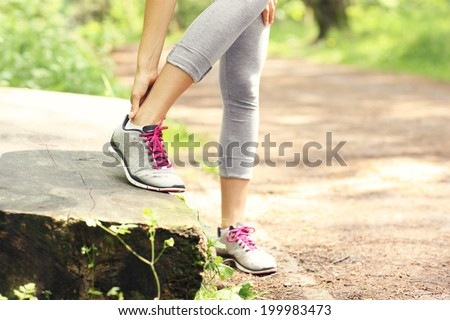 A picture of a jogger having problems with ankle in the forest - stock photo