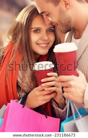 A picture of a joyful couple shopping in the mall with coffee - stock photo