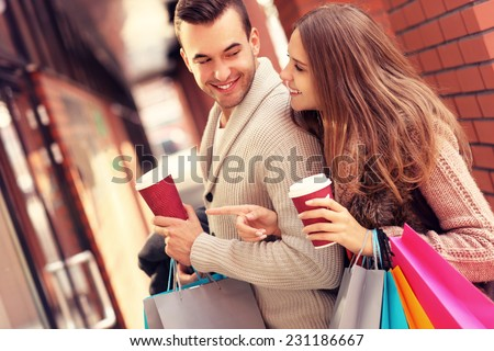 A picture of a joyful couple window shopping in the mall with coffee - stock photo