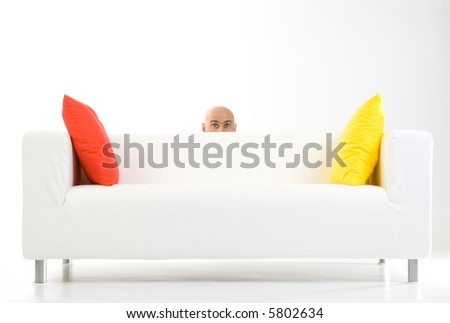 A picture of a man, peeping up from behind a white sofa with an orange and a yellow pillow on it. - stock photo