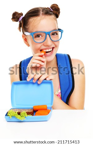 A picture of a schoolgirl eating healthy lunch over white background - stock photo