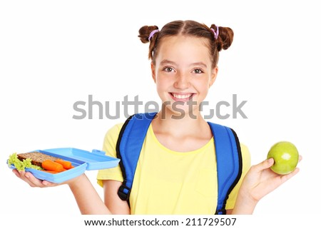 A picture of a schoolgirl having healthy lunch over white background - stock photo