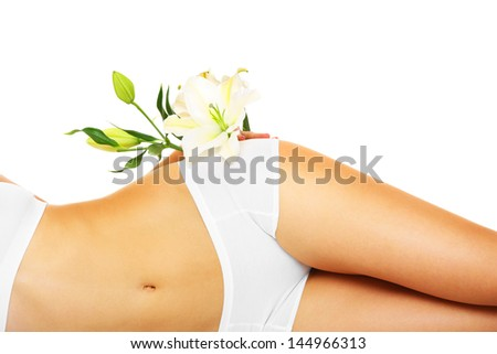 A picture of a slim female belly and a flower over white background - stock photo