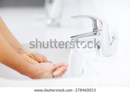 A picture of a woman cleaning hands in the bathroom - stock photo
