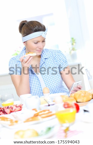 A picture of a woman eating breakfast and texting - stock photo