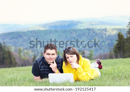 A picture of a young couple and laptop on the grass in the mountains - stock photo