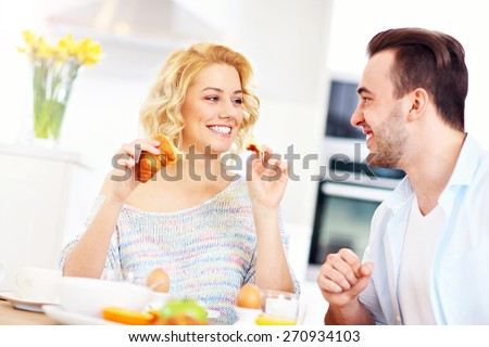 A picture of a young couple eating breakfast in the kitchen - stock photo