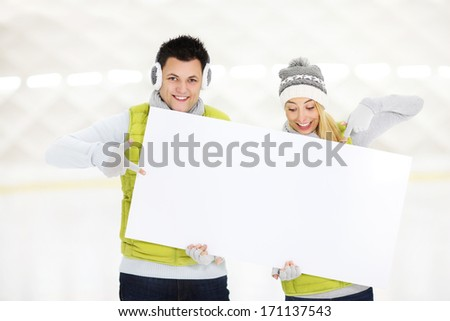 A picture of a young couple showing a white board in the ice rink - stock photo