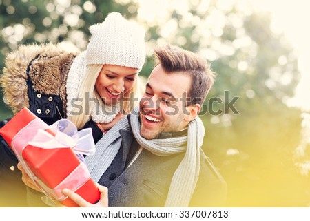 A picture of a young couple with a present in the park - stock photo