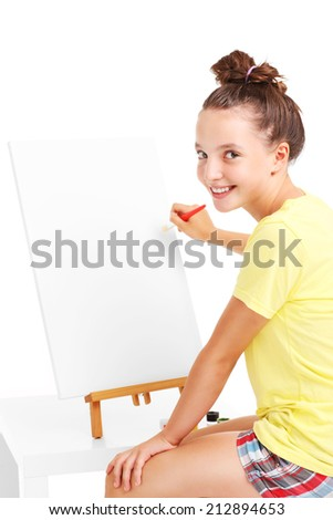 A picture of a young girl painting on an easel - stock photo