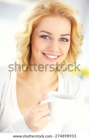 A picture of a young happy woman drinking coffee in the kitchen - stock photo