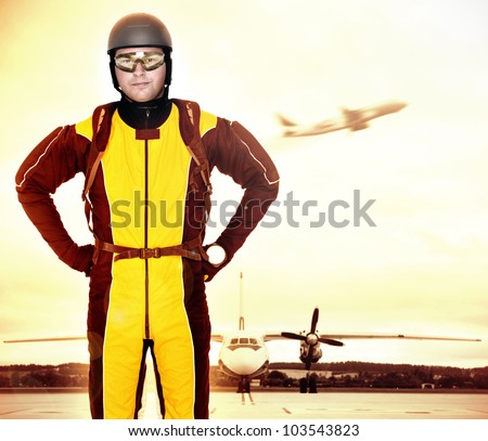 A picture of a young parachutist standing in front of a plane at the apron - stock photo