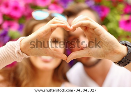A picture of a young romantic couple showing a heart shape - stock photo