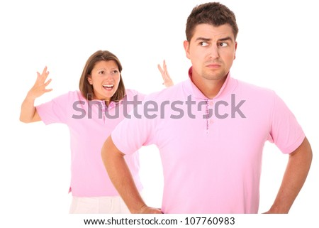A picture of a young sad man standing over white background and his wife shouting in the back - stock photo