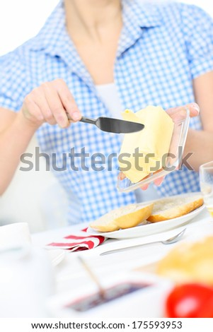 A picture of a young woman buttering a toast in the kitchen - stock photo