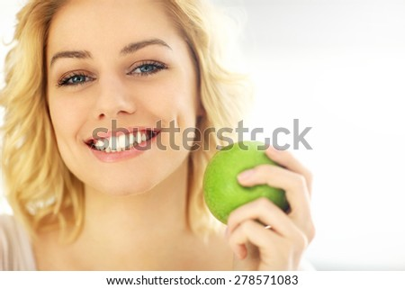 A picture of a young woman eating an apple at home - stock photo