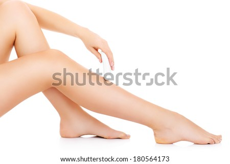 A picture of a young woman removing hair from  her legs over white background - stock photo