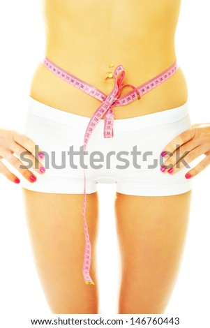 A picture of a young woman with a tape measure bow on her belly over white background - stock photo