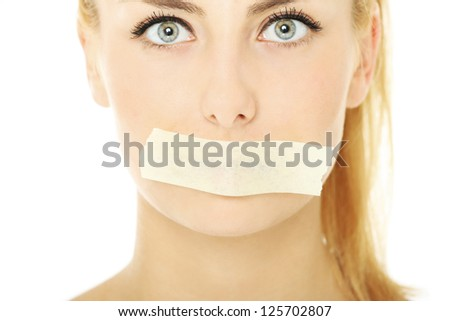 A picture of a young woman with a tape on her mouth over white background - stock photo