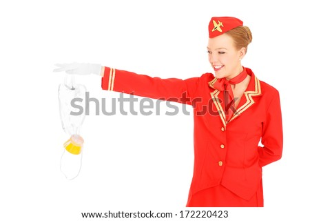 A picture of an attractive stewardess presenting an oxygen mask over white background - stock photo