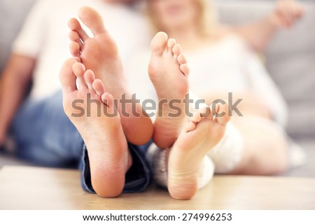 A picture of barefeet couple lying on a sofa - stock photo