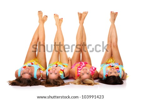 A picture of four girlfriends lying on the floor in hawaiian skirts with their legs up over white background - stock photo
