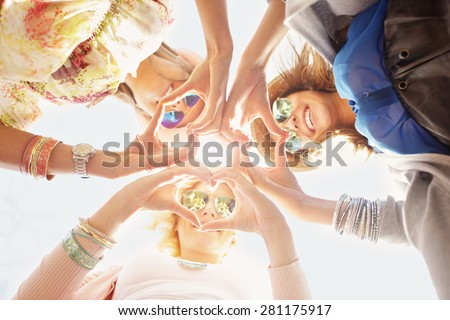 A picture of group of happy friends showing hearts - stock photo