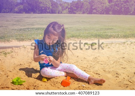 A  picture of little girl playing sand at public park ,filtered color tone in picture. - stock photo