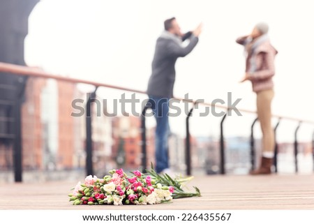 A picture of lost flowers and a couple arguing in the background - stock photo