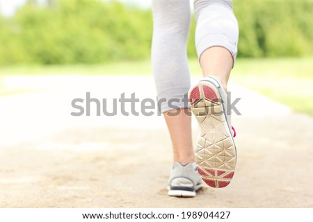 A picture of the back of  jogger's legs on the path in the park - stock photo
