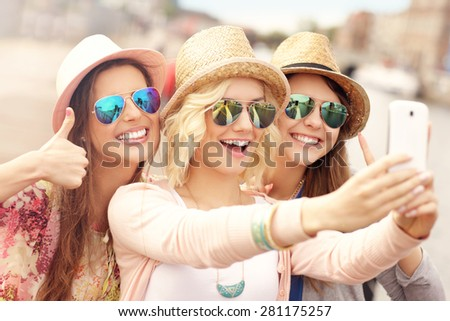 A picture of three friends taking selfie in the city - stock photo